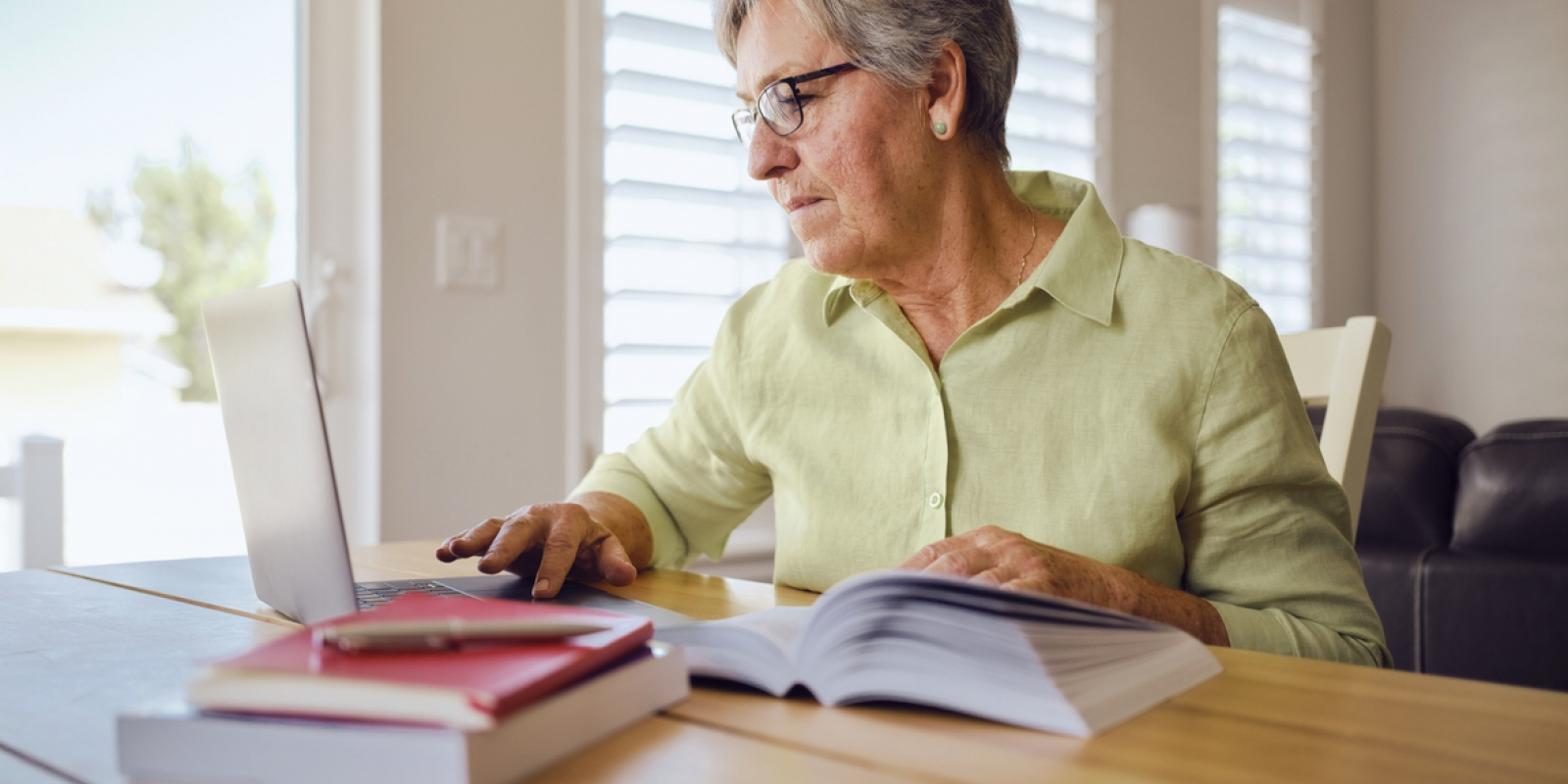 Older woman studying with a book and computer