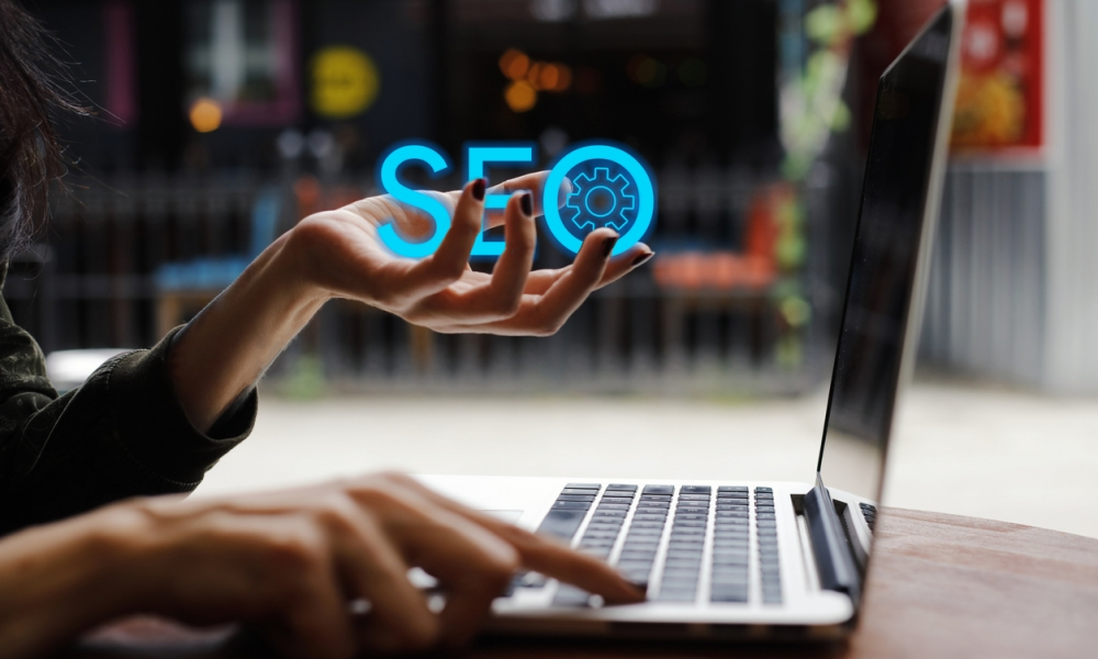 persons hand holding the word SEO and computer