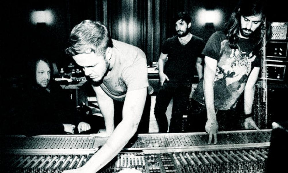 black and white photo of band at mixing board
